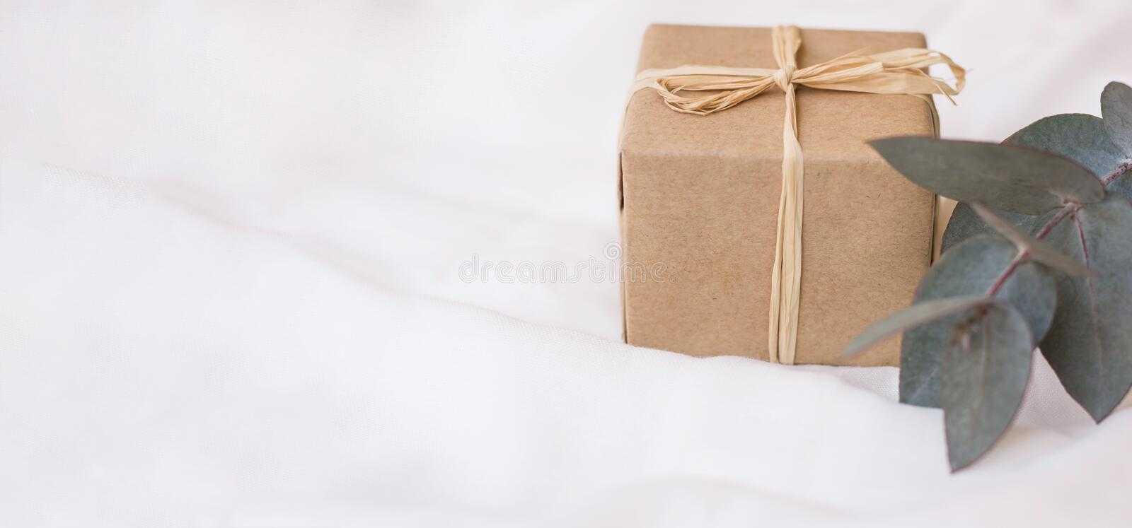 Long banner header gift box in craft paper branch of silver dollar eucalyptus on white linen fabric. Template for store coupon. Long banner header gift box in stock photos