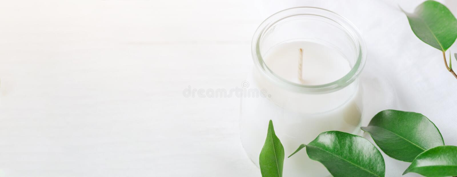 Long Banner for Organic Cosmetics Wellness White Candle in Glass Jar Fresh Tree Branches with Green Leaves on Wood Background. Spa. Body Care Meditation Purity stock photos