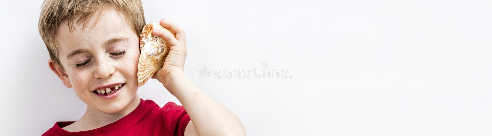 Long banner of smiling imaginative child listening to ocean shell stock photos