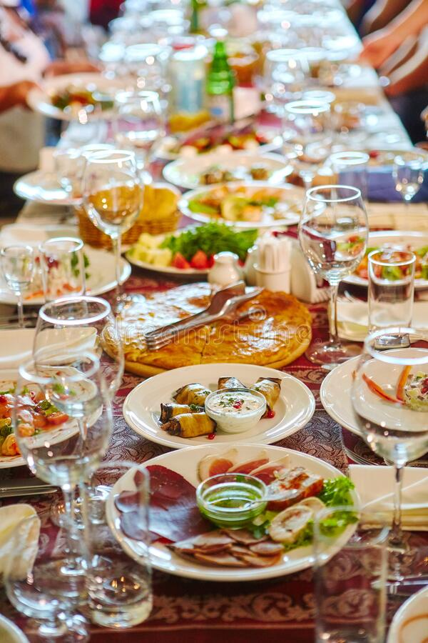 Long Banquet table. Drinks and snacks on the table.  People are sitting at the table. Concept of joint celebrations. Long Banquet table. Drinks and snacks on the royalty free stock image