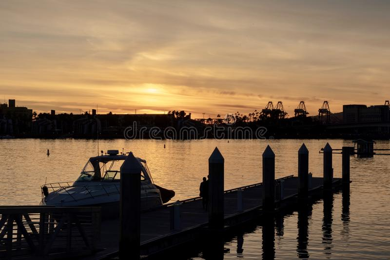 Long Beach Harbor during sunset. Boat at a pier in the Long Beach harbor during sunset stock photo