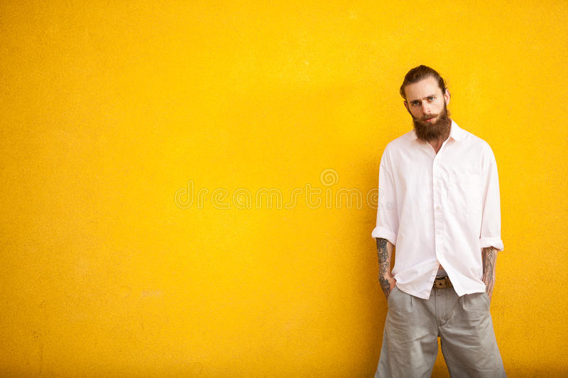 Long bearded hipster on yellow wall. In outside fashion shooting stock photo