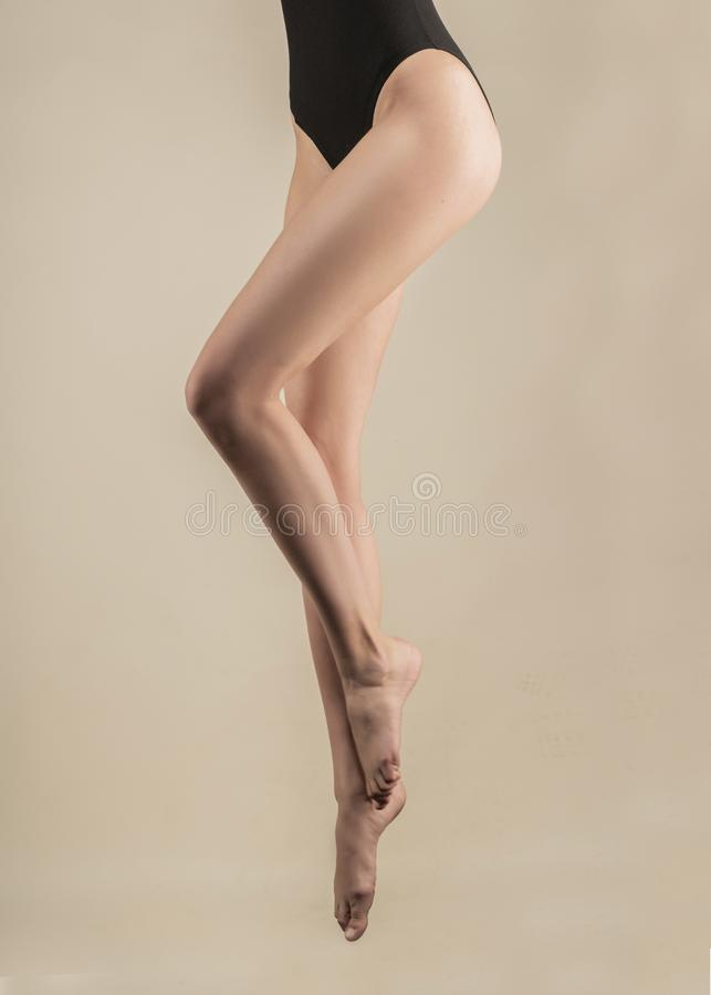 Long beautiful slender female legs hanging in the air in the jump. The girl is dressed in a black body. Isolated on a light stock photos