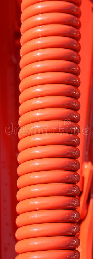 Long big red industrial spring of a car. Very long huge red industrial spring of a car royalty free stock photography