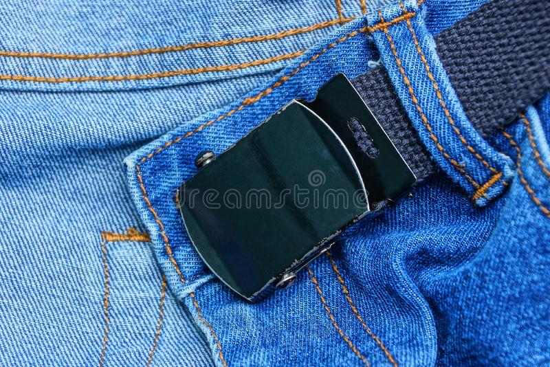 Black belt with a metal buckle on a blue denim pants. Long black belt with a metal buckle on a blue denim pants royalty free stock images