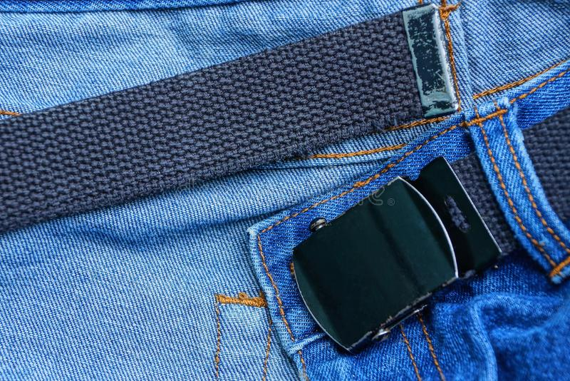 Black belt with a metal buckle on a blue denim pants. Long black belt with a metal buckle on a blue denim pants stock photography