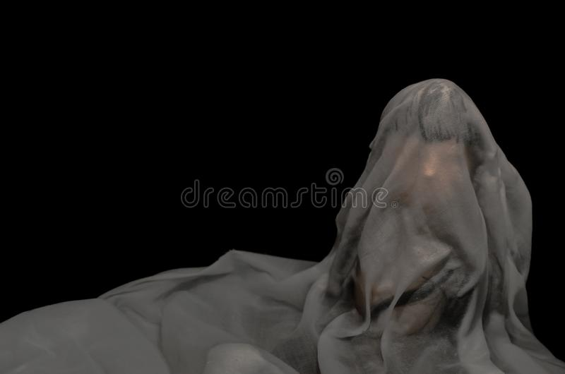 Long black hair doll cover with white sheet drown in water on dark background. Minimal Halloween scary concept stock image