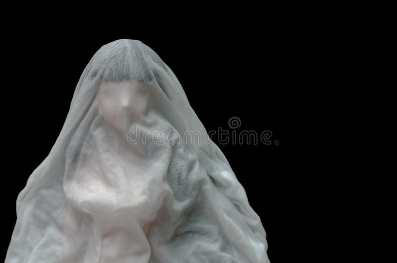 Long black hair doll cover with white sheet drown in water on dark background. Minimal Halloween scary concept royalty free stock photo