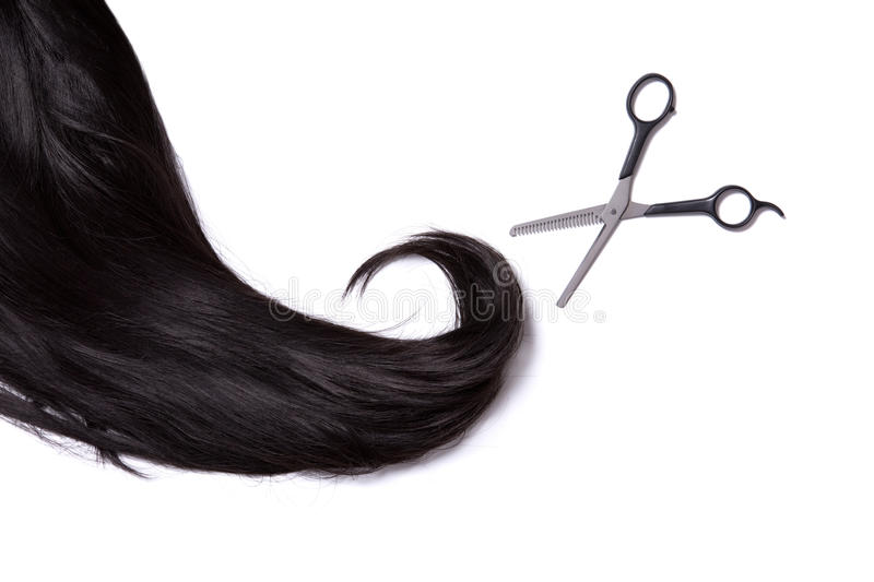 Long black shiny hair with professional scissors royalty free stock photography