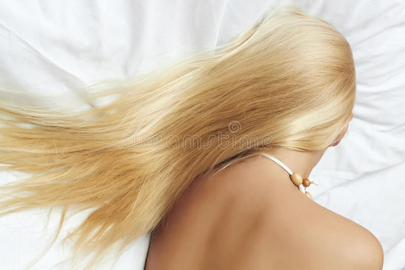 Long blond hair. beautiful blond woman sleeping in the bed stock photography