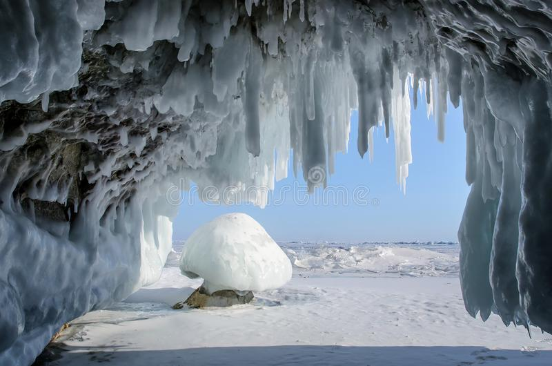 Long blue icicles in the ice cave at coastal cliffs. royalty free stock images