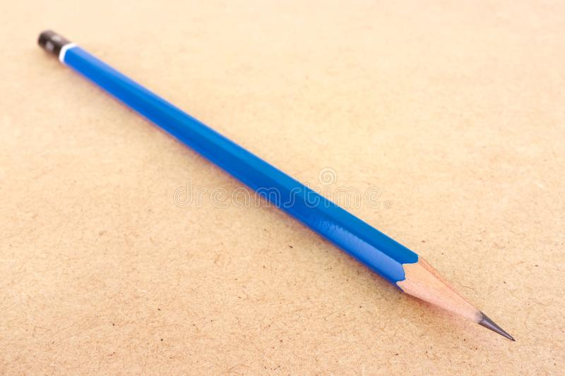 Long blue pencil on wood background. Close-up of one long sharp blue lead graphite school pencil on a wood textured board background royalty free stock photography