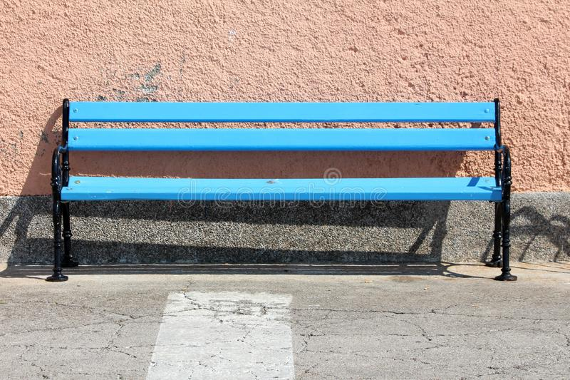 Long blue wooden public bench with black iron frame mounted on side of paved sidewalk in front of house wall. On warm sunny day royalty free stock photography