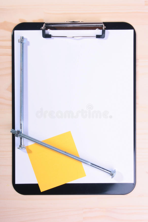 Long bolts. Two long bolts for fixture on blank clipboar with a pure clean sheet of a paper for records stock photos