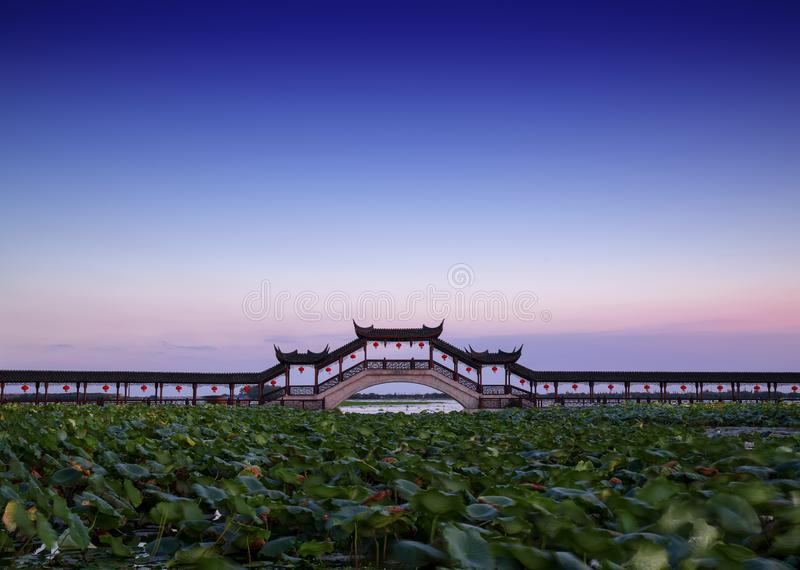 Long bridge in the aicent town of Jiangsu China, jinxi. Jinxi, an aicent town in Kunshan Jiangsu China. Image was shooted when sunset byside a lake. A boot in royalty free stock images