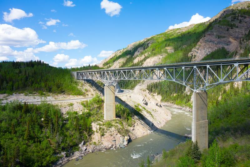 A long bridge over a canyon in alaska. A river crossing for vehicles and passage for trains as seen near anchorage in the springtime stock images