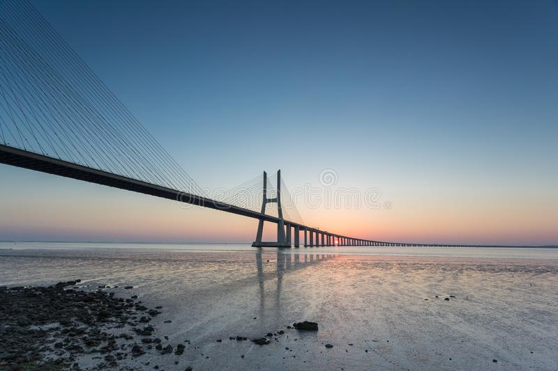 Long bridge over tagus river in Lisbon at sunrise royalty free stock photo