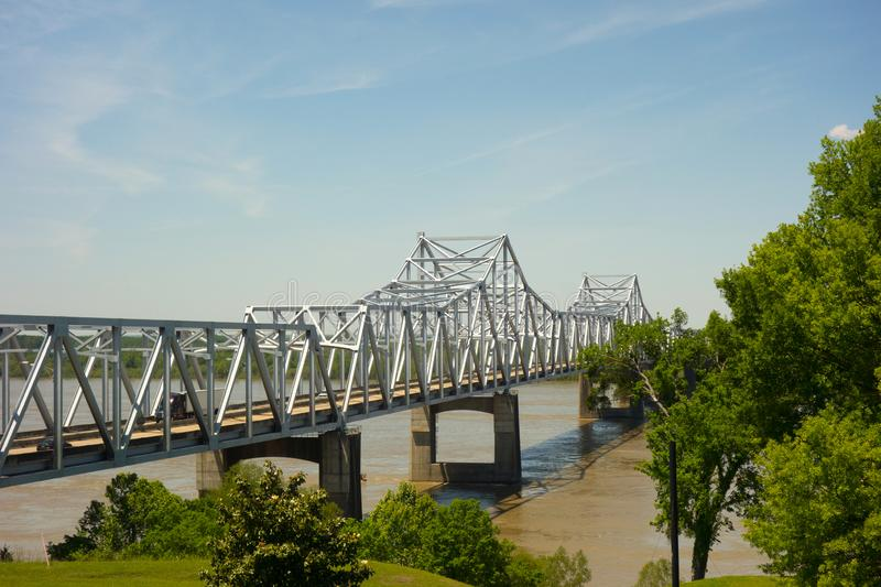 A long bridge spanning a wide river in the United States. A steel vehicular bridge supported by cement pillars over the mighty Mississippi in the springtime stock image