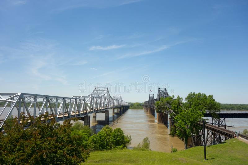 Long bridges spanning a wide river in the United States. A steel vehicular bridge supported by cement pillars over the mighty Mississippi alongside the old stock photo