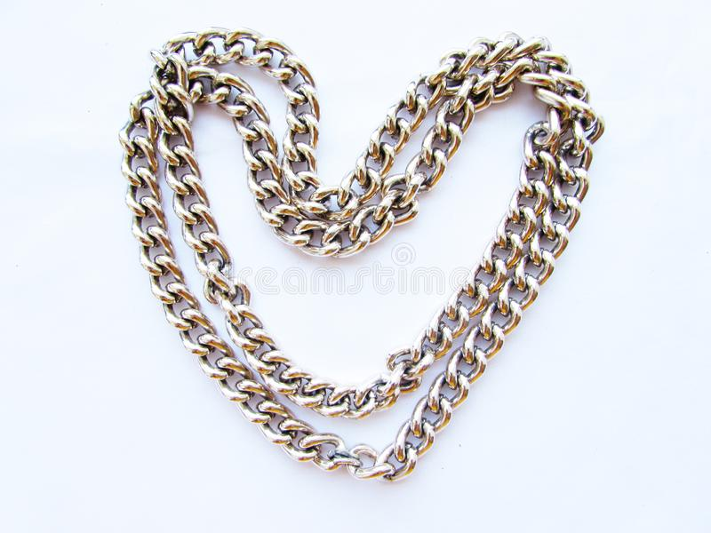 Long metal chain with large links in the shape of a heart isolated object on a white background. Long chain with large links in the shape of a heart isolated royalty free stock images
