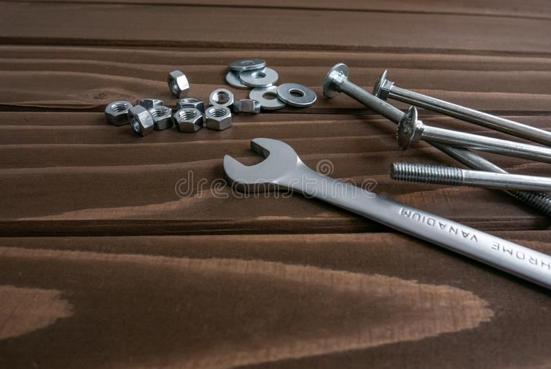 Long chrome bolts and nuts lying on wooden planks beside the steel wrench. Long chrome bolts and nuts lying on dark brown wooden planks beside the steel wrench royalty free stock photos