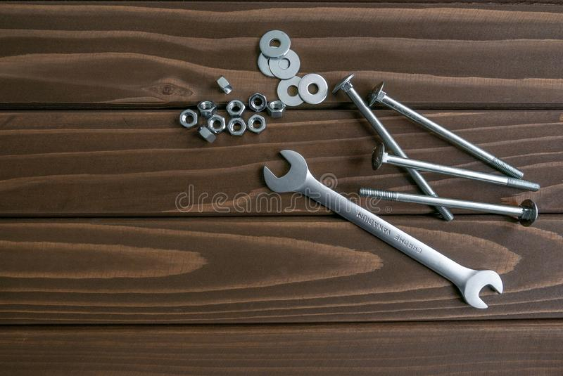 Long chrome bolts and nuts lying on wooden planks beside the steel wrench. Long chrome bolts and nuts lying on dark brown wooden planks beside the steel wrench royalty free stock photography
