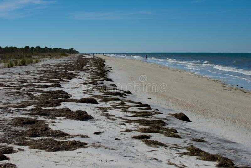 Long coast line of beach and rolling waves. Long florida coastline of beaches with rolling in waves blues skies and sandy beaches stock photo