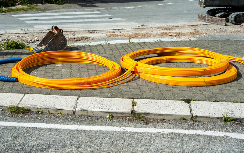 Long coils of orange plastic pipes stock photos