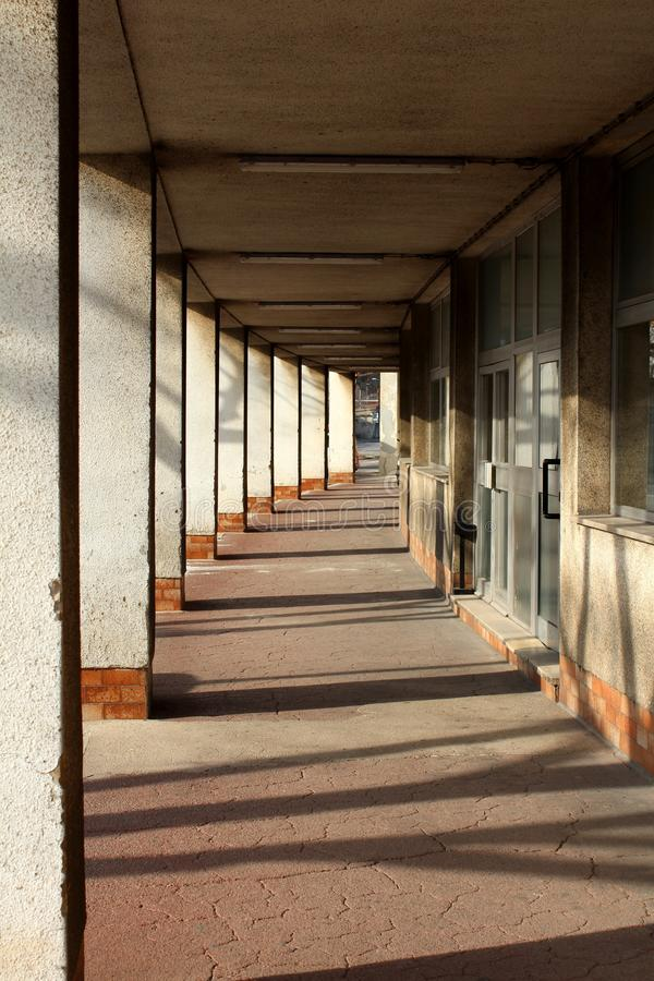 Long concrete pillars hallway supporting top floor and large entrance doors on side mounted on cracked floor of abandoned stock photos