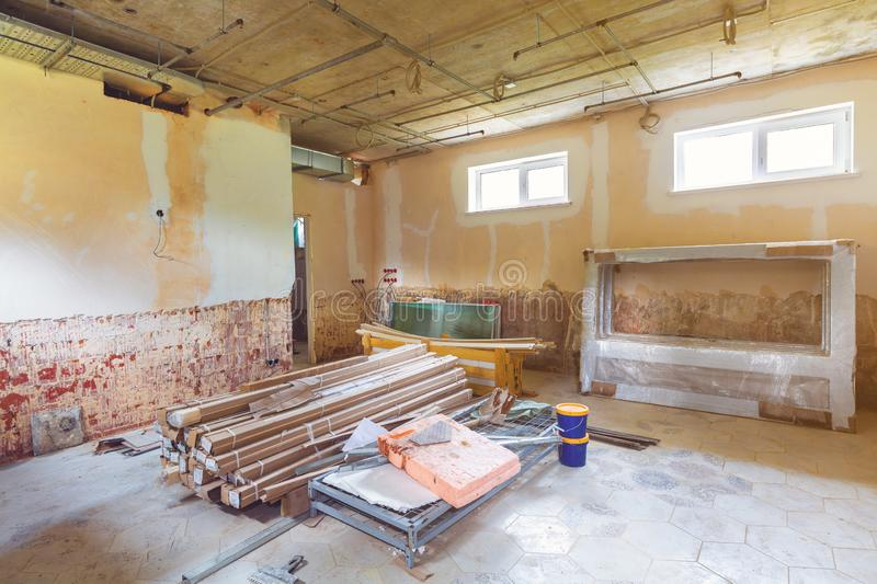 Long corridor and room with construction materials, cable trays and walls with not installed electrical cables in a royalty free stock photo