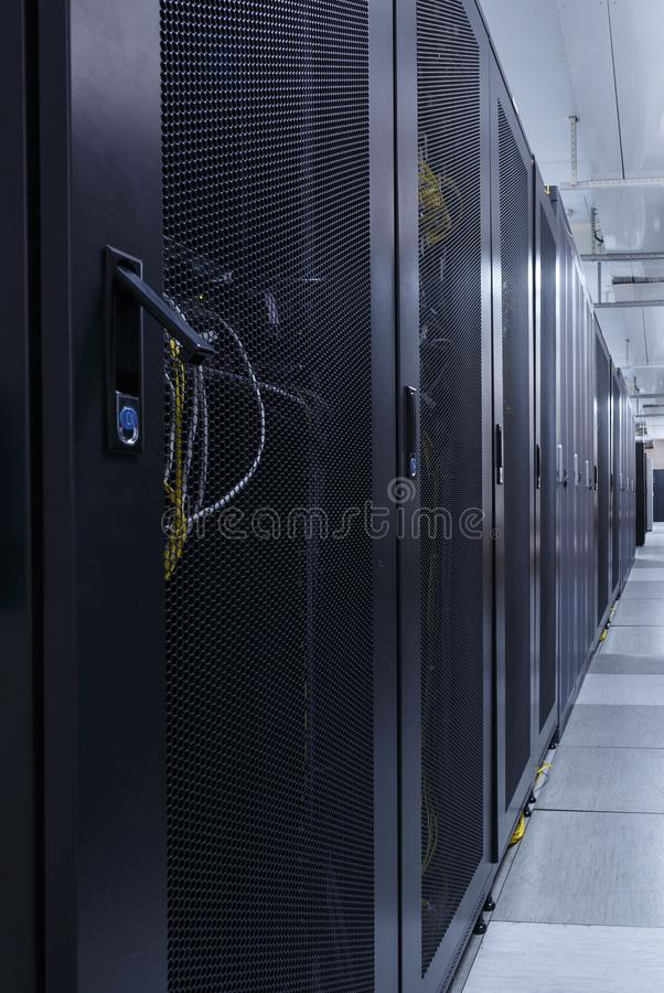 Long corridor in server room with rows of hardware in big data center. Technical equipment and supercomputers in cabinets under closed grid door stock photos