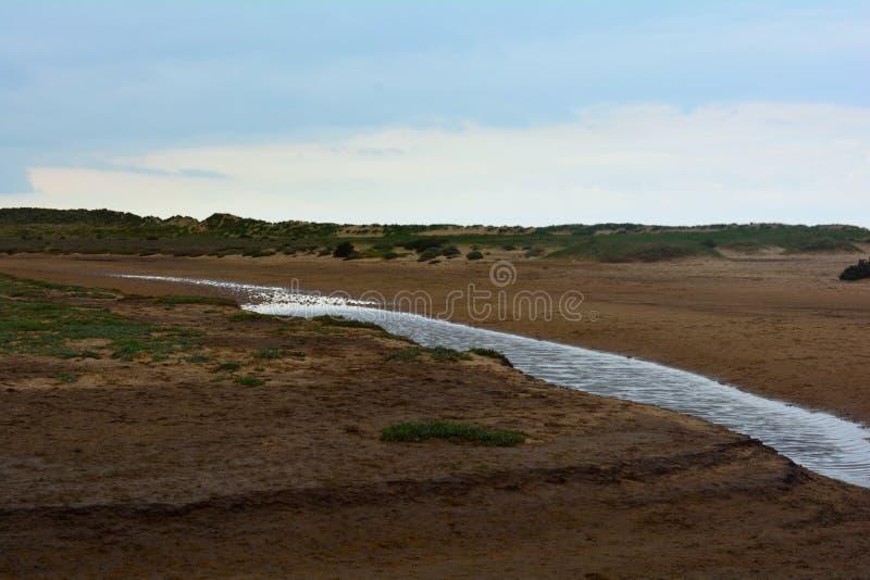 Long courant côtier à la plage, mer du nord, plage de Holkham, Royaume-Uni image libre de droits