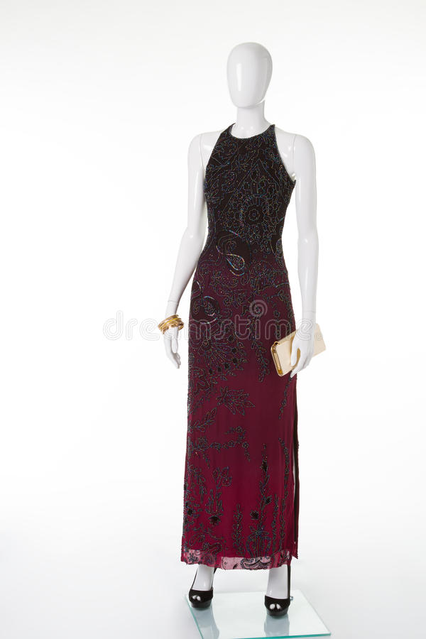 Long dark maroon dress. Long dark maroon dress with patterns on the shop window. Evening dress white mannequin stock images