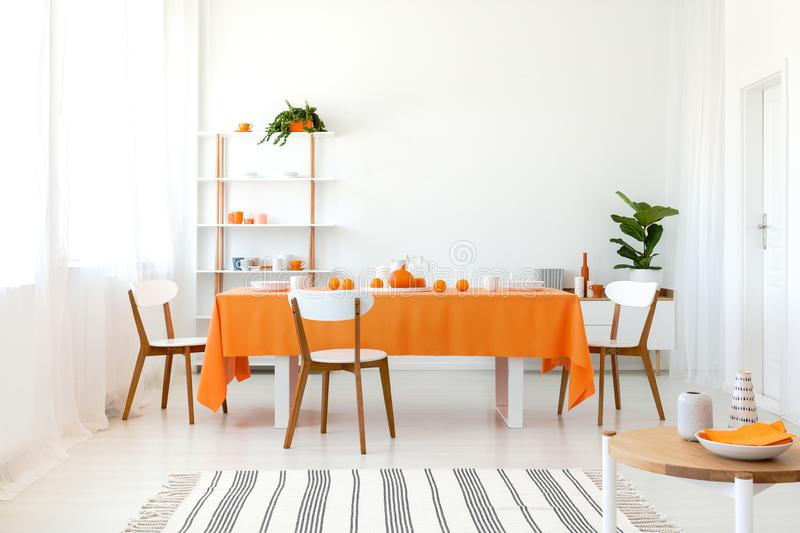 Long dining room table covered with orange tablecloth and comfortable white chairs stock photos