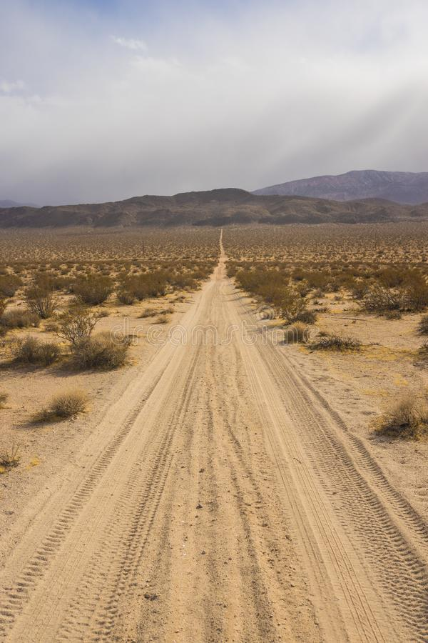 Long Dirt Desert Road to Mountains. Long straight dirt road leads across the desert and into mountains covered by clouds royalty free stock images