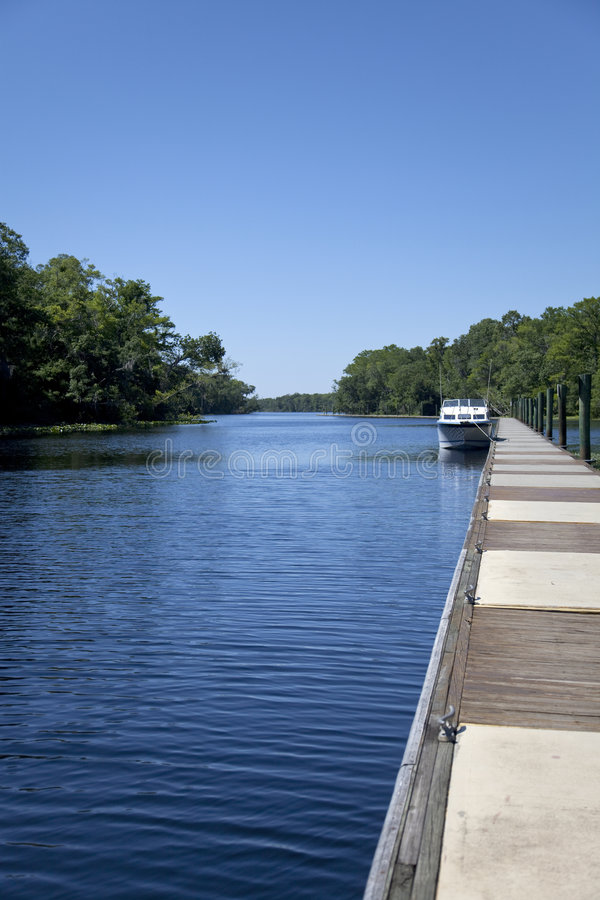 Long Dock with Boat on a River royalty free stock image