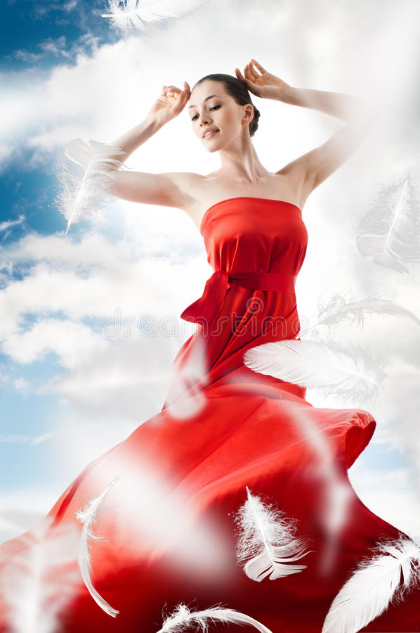 Long dress. Beautiful young woman in red long dress royalty free stock photography