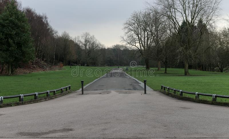 Long Driveway away from the hotel. The long and straight tarmac driveway leading into the distance between two areas of grass stock photo