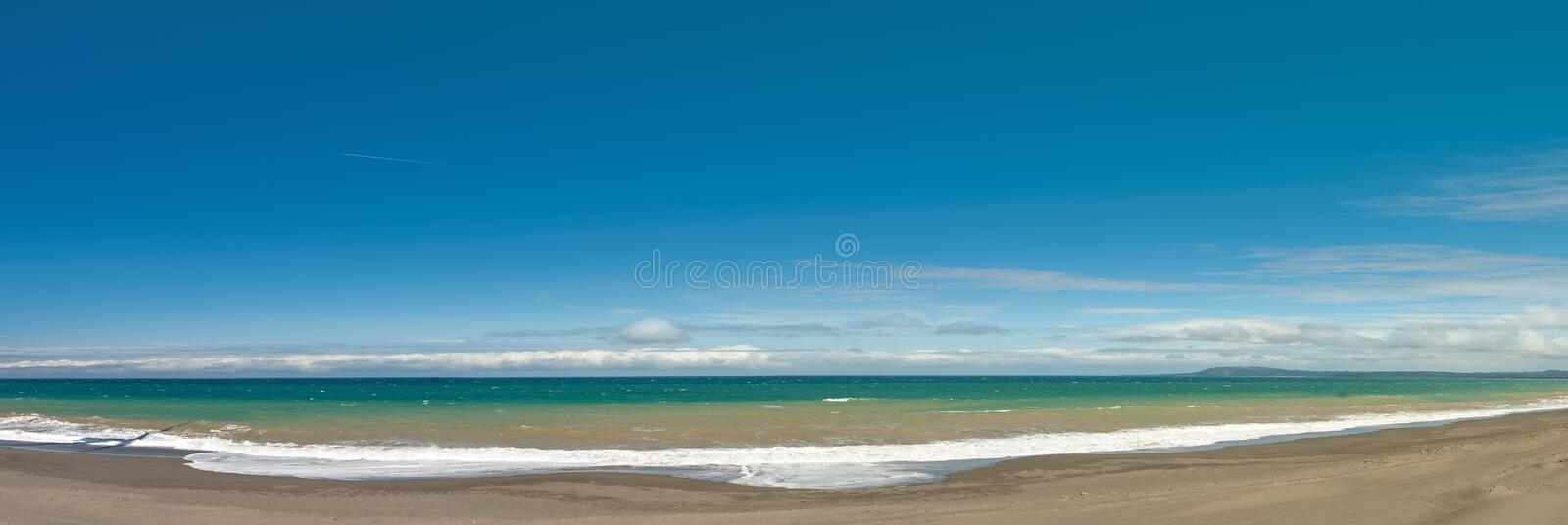 Long and empty ocean coast beach panoramic view background. With blue sky and sea waves royalty free stock photo