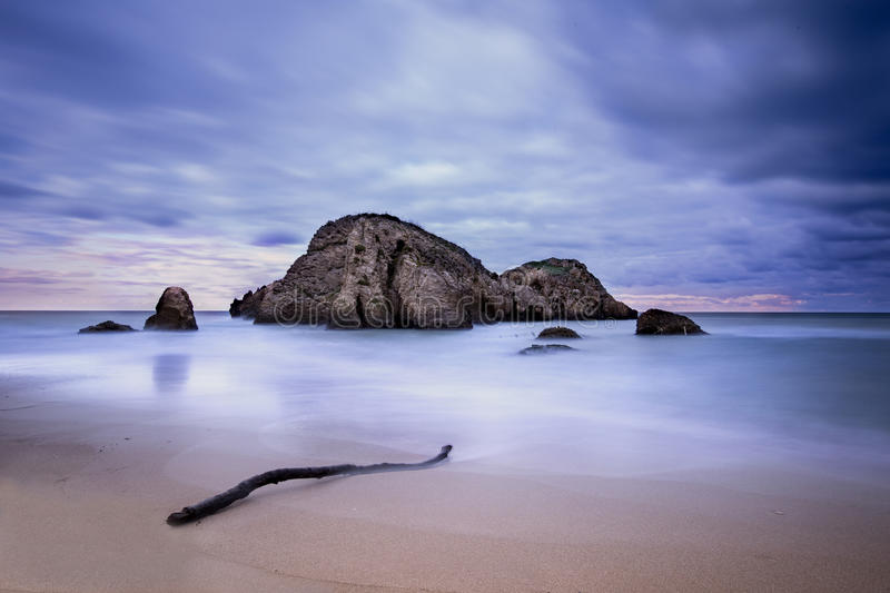 Long Exposure Beach. Horizontal long exposure photo of a beach from Sile Turkey / Turkiye. A large rock and branch is visible. Sea is silky smooth stock image