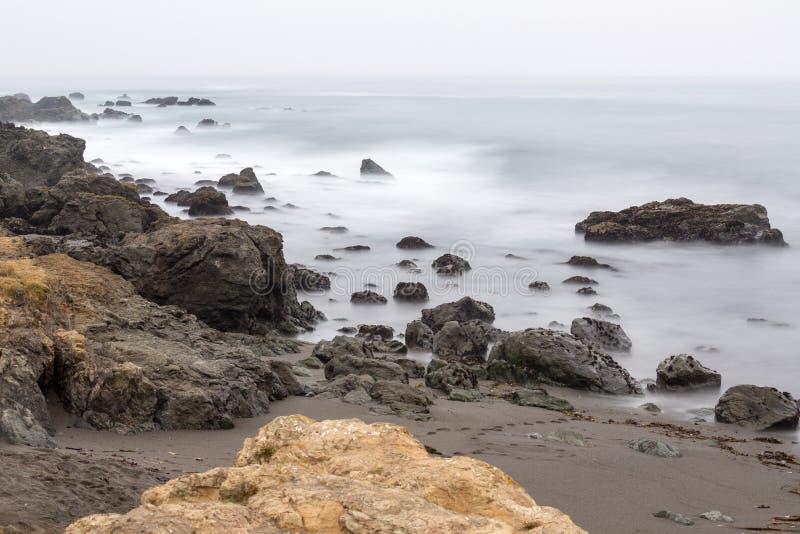Long exposure of beach rocks. In the fog stock photos