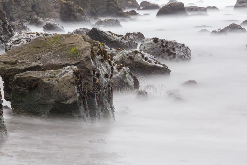 Long exposure of beach rocks. In the fog royalty free stock images
