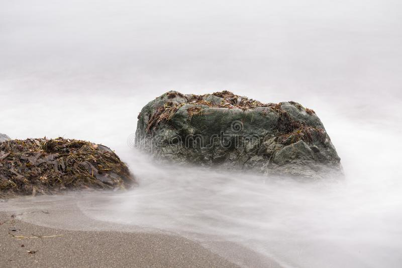 Long exposure of beach rocks. In the fog stock photography
