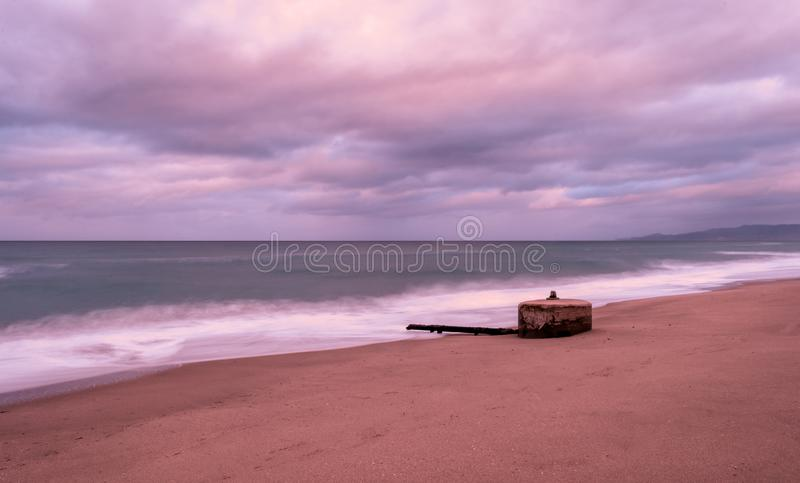 Long exposure of beach in winter at the sunset. Long exposure of beach in a cloudy sunset of winter royalty free stock photo