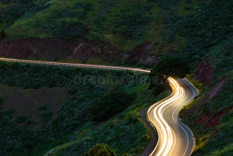 Long exposure car trails on windy mountain road stock image