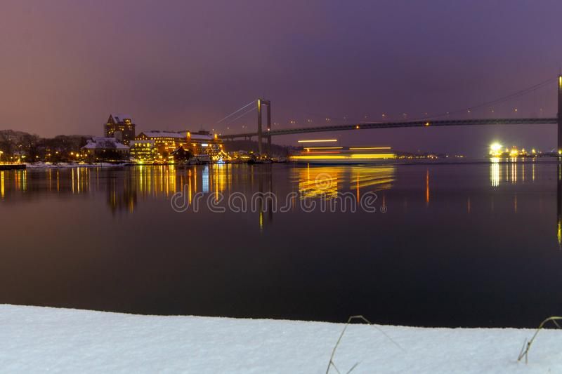 Long exposure city and bridge photo. Long exposure photo of bridge and buildings with moving boat. Night time photo with reflections in water royalty free stock photo
