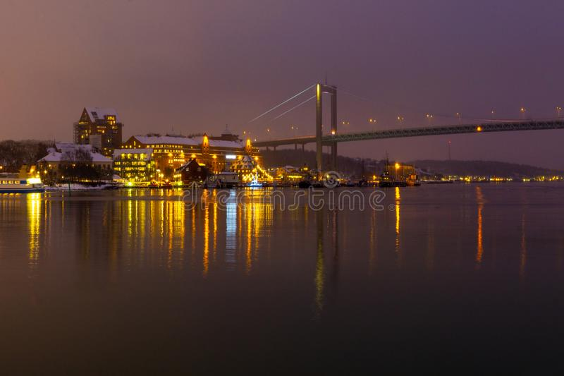 Long exposure city and bridge photo. Long exposure photo of bridge and buildings with moving boat. Night time photo with reflections in water stock images