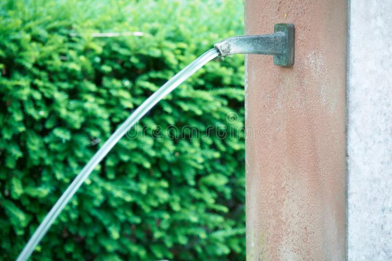 Long exposure of a closeup waterjet at a public fountain with low depth of field in front of a green hedge stock photos