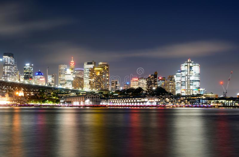 Colorful light reflections on the water from the central business district in Sydney, Australia at night. Long exposure of colorful light reflections streaked stock photo