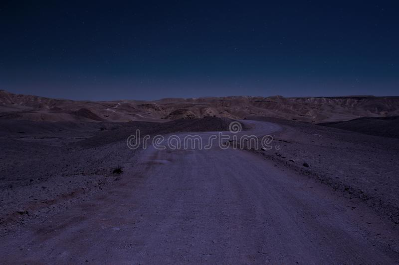 Long exposure desert night scenery landscape with stars blue sky photography of wasteland country side gravel road go to mountains royalty free stock images